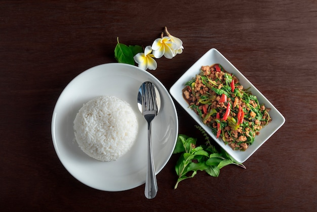 Reis mit gebratenem schweinefleisch mit basilikumblatt im weißen teller auf dunkelbrauner tabelle