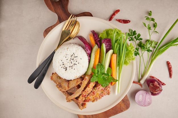 Reis mit gegrilltem schweinehals. gegrilltes schweinefleischsalat thailändisches essen mit kräutern und gewürzen zutaten, traditionelles nordöstliches essen köstlich mit frischem gemüse, scharfes und würziges stück gegrilltes schweinefleischmenü asiatisches essen.