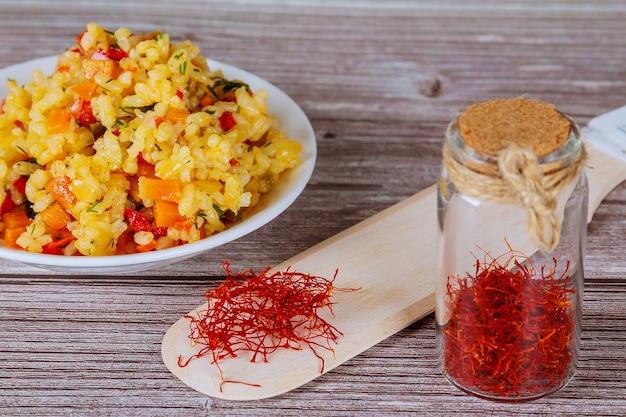 Reis mit gemüse mit safran auf einem weißen teller auf einem hölzernen hintergrund