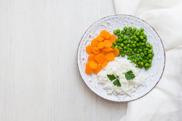 Reis mit gemüse und grüner petersilie auf platte mit weißem stoff