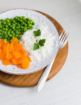 Reis mit gemüse und petersilie auf platte auf hölzernem brett