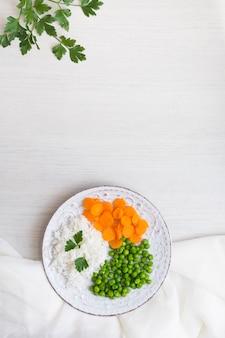 Reis mit gemüse und petersilie auf platte mit weißem stoff