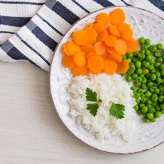 Reis mit gemüse und petersilie auf weißer platte