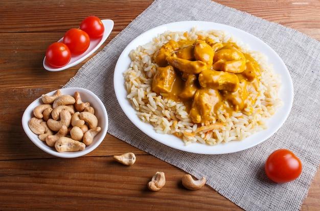 Reis mit hühnercurrysoße mit acajoubaum auf braunem hölzernem hintergrund.