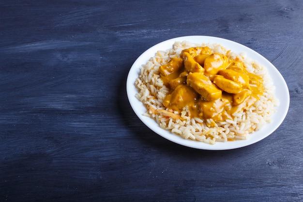 Reis mit hühnercurrysoße mit acajoubaum auf schwarzer holzoberfläche.