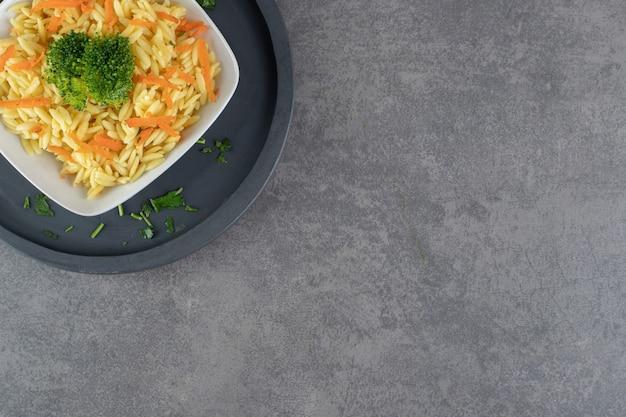 Reis mit karottenscheiben und brokkoli auf weißem teller. foto in hoher qualität