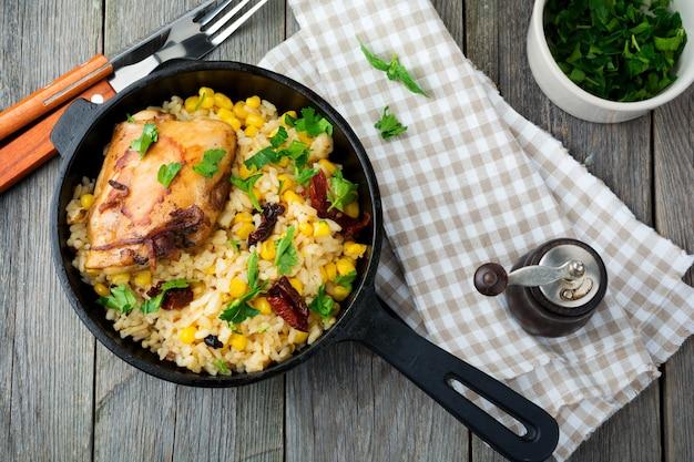 Reis mit mais, sojasauce und gebratenem hähnchenschenkel auf einer gusseisernen pfanne. draufsicht