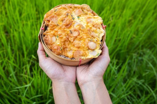 Reis mit omelettwurst auf traditionellen bambuswebartplatten an hand