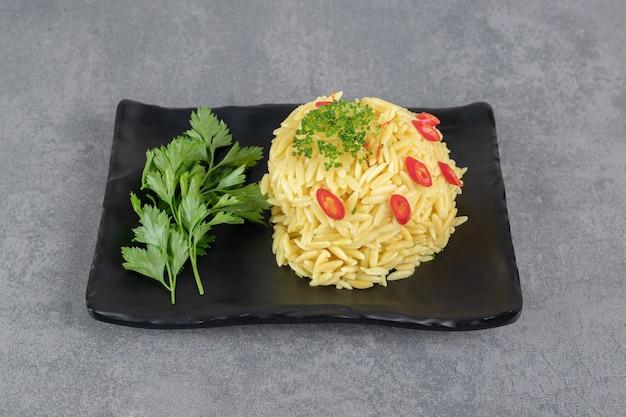 Reis mit pfefferscheiben und grüns auf schwarzem teller. foto in hoher qualität