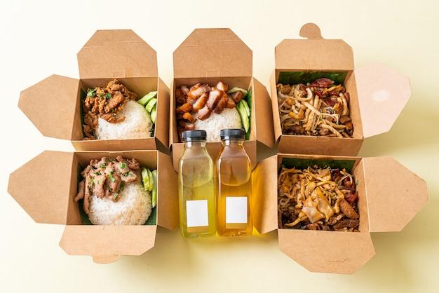 Reis mit schweinefleisch und nudeln in lieferboxen mit öl und essig