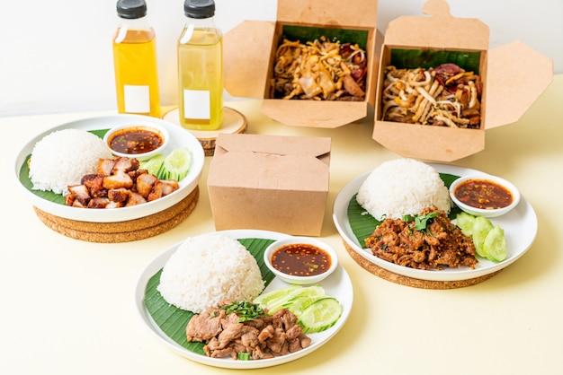 Reis mit schweinefleisch und nudeln in lieferboxen