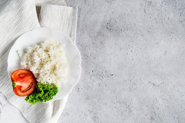 Reis mit tomate und petersilie auf weißer serviette