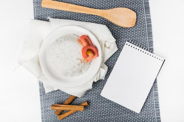 Reis mit tomatenscheibe und zimtstangen mit spachtel und notizblock auf placemat