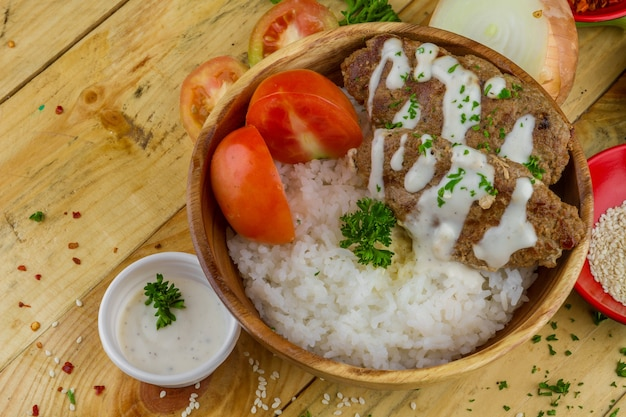 Reis, schnitzel, tomaten mit sauce und gemüse in einer holzschale serviert