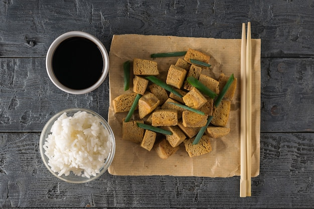 Reis, sojasauce, essstäbchen und gegrillter tofukäse auf einem holztisch. gegrillte käse vorspeise. flach liegen.