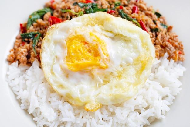 Reis überbacken mit gebratenem schweinefleisch, basilikum und spiegelei