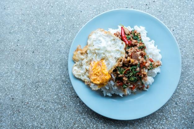 Reis überstieg mit angebratenem schweinefleisch und basilikum im weißen teller auf holztisch.