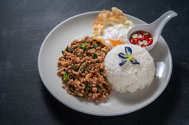 Reis überstiegen mit angebratenem schweinefleisch und basilikum auf hölzernem. thai essen