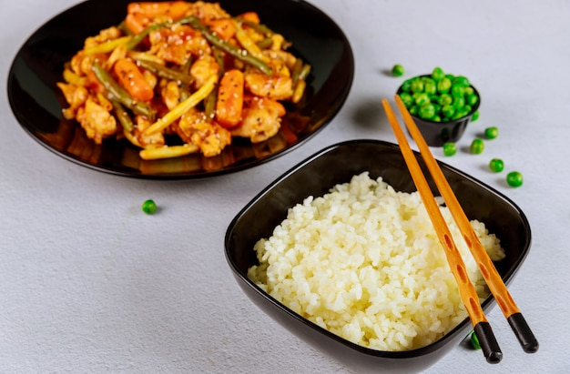 Reis und gebratenes huhn mit babykarotten und grünen bohnen umrühren