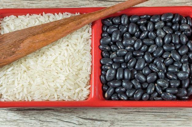 Reis- und schwarze bohnenrohöl im roten behälter auf hölzernem hintergrund