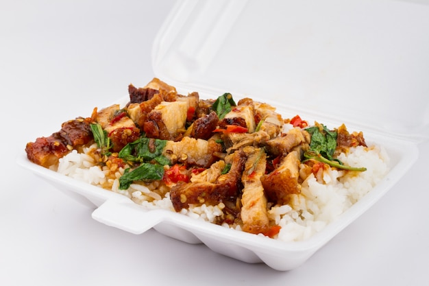Reis und schweinefleisch gebraten mit heiligem basilikum auf weißem, thailändischem essen,