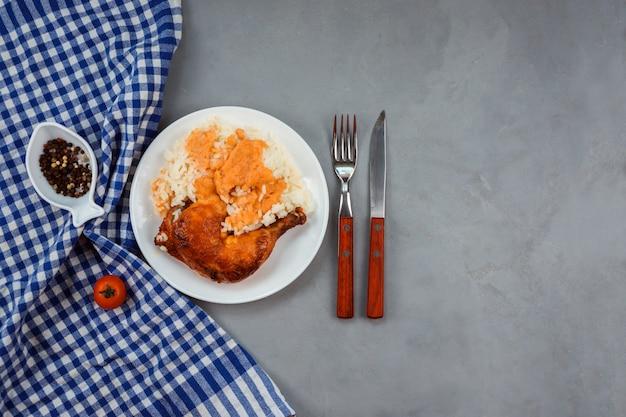 Reis unter currysauce mit gebratenem hähnchenschenkel serviert auf dem weißen teller. blaues handtuch, pfeffer in der fischförmigen schüssel, messer und gabel schmücken grauen hintergrund.