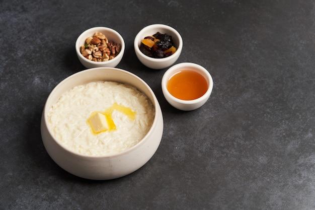 Reisbrei mit milch, rosinen, honig und nüssen in einer schüssel.