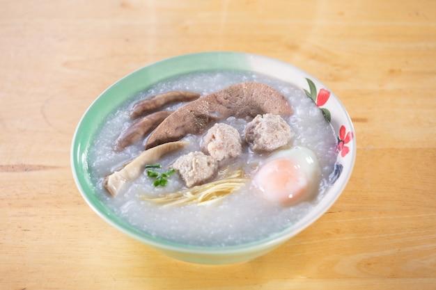 Reisbrei mit schweinefleisch auf holztisch