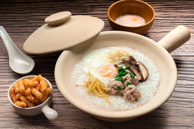 Reisbrei mit weich gekochtem ei, gehackte schweinekugel in scheiben geschnittener shiitake-pilz in scheiben geschnittener ingwer im tontopf, serviert mit belag knuspriger patongo frittierter teig, bekannt als thailändisches berühmtes frühstück famous