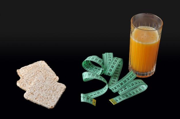 Reiscracker, ein glas orangensaft und maßband