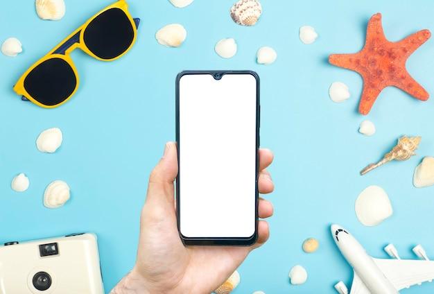 Reise-app-konzept leerer bildschirm smartphone auf farbigem hintergrund mit reiseartikeln sonnenbrille airp ...