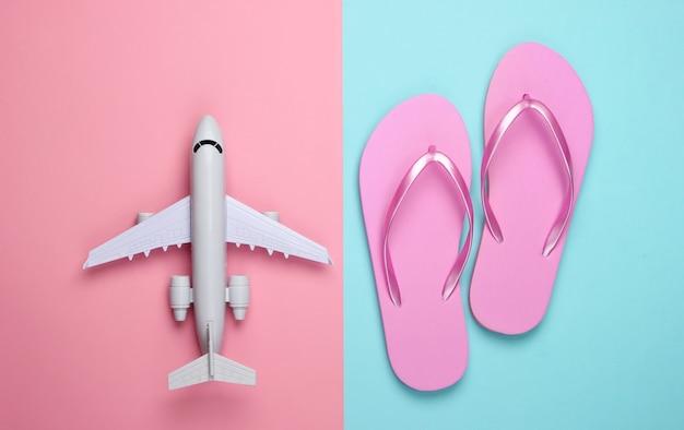 Reise flach legen komposition. flugzeugfigur, flip flops auf rosa blau pastell.