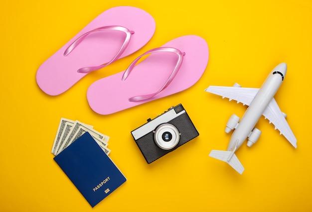 Reise flach legen komposition. flugzeugfigur, flip flops, kamera, pass auf einem gelb