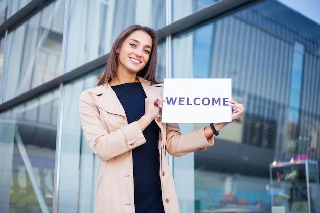 Reise, frauengeschäft mit dem plakat mit willkommensmitteilung