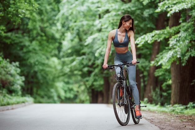 Reise haben. weiblicher radfahrer auf einem fahrrad auf asphaltstraße im wald am tag