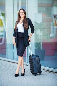 Reise, junge frau geht am flughafen am fenster mit dem koffer, der auf fläche wartet