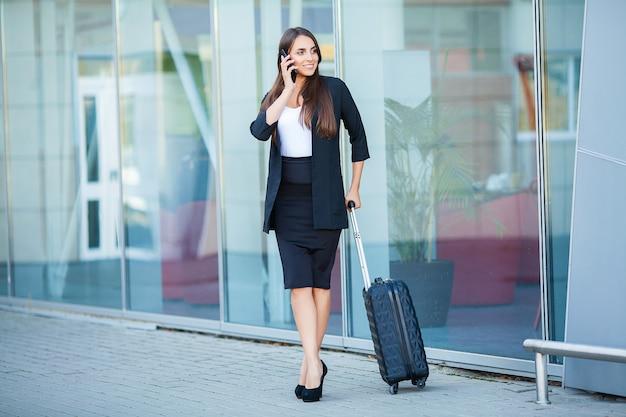 Reise. junge frau geht am flughafen am fenster mit dem koffer, der auf fläche wartet