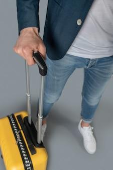 Reise, koffer. mann in dunkler jacke und jeans, der den griff eines gelben reisekoffers auf rädern hält, kein gesicht