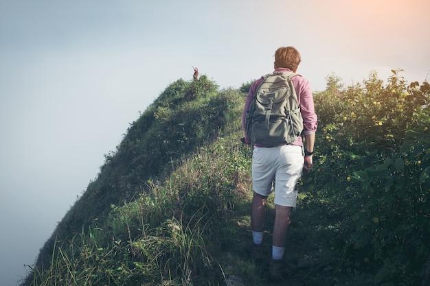 Reise-konzept. junge touristen mit den rucksäcken, die talansicht von der spitze eines berges genießen