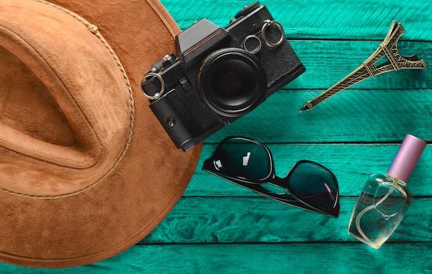 Reise nach frankreich, paris. filzhut, filmkamera, sonnenbrille, parfümflasche, andenkenstatue des eiffelturm-layouts auf einem farbigen holztisch. leidenschaft für reisen, fernweh-konzept. flach liegen.