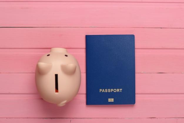 Reise oder auswanderung. reisepass mit sparschwein auf rosa holzoberfläche. draufsicht