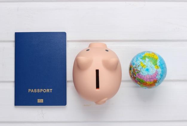 Reise oder auswanderung. reisepass mit sparschwein, globus auf weißer holzoberfläche. draufsicht. flach liegen
