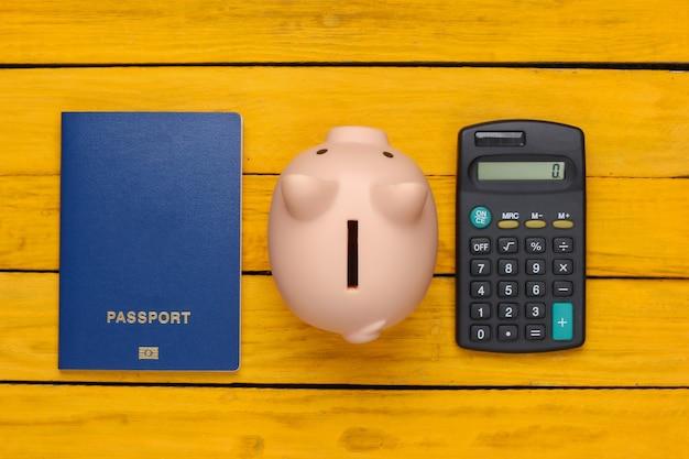 Reise oder auswanderung. reisepass mit sparschwein, taschenrechner auf gelber holzoberfläche. draufsicht