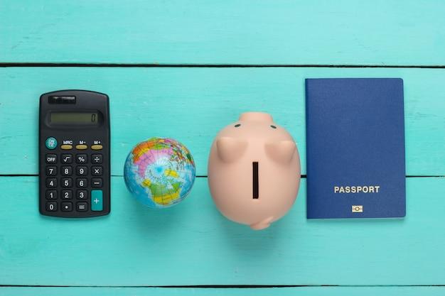 Reise- oder auswanderungsidee. reisepass mit sparschwein, globus, taschenrechner auf blauer holzoberfläche. draufsicht