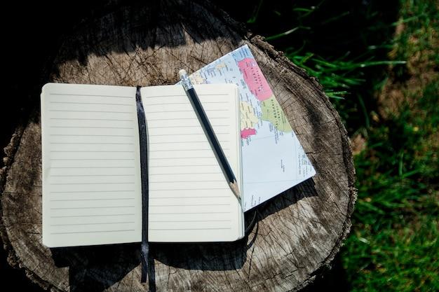 Reise planen. karte, notiz und bleistift auf holz