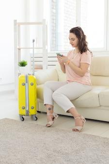 Reise-, reise- und urlaubskonzept - frau mit gelbem koffer wartet auf das taxi