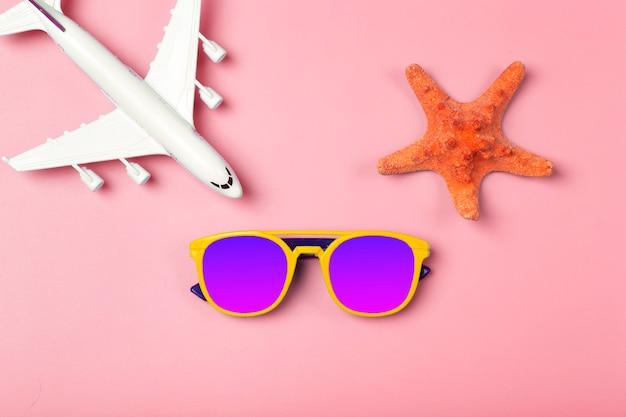 Reise-sommer-sonnenbrillen-flugzeug und strand-accessoires auf einer farbigen rosa hintergrundtour ...