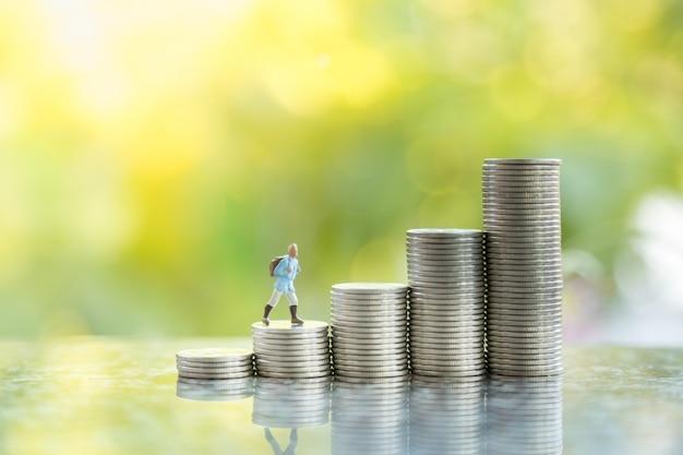 Reise-, spar- und planungskonzept. schließen sie oben von reisenden miniaturfigur menschen mit rucksack, der oben auf stapel von münzen mit kopienraum und grünem naturhintergrund geht.
