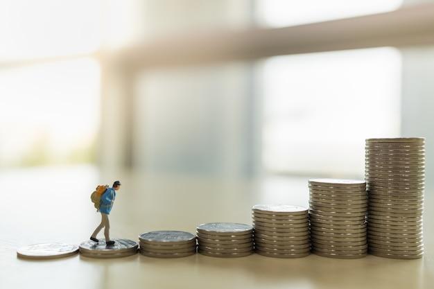 Reise-, spar- und planungskonzept. schließen sie oben von reisenden miniaturfigur menschen mit rucksack, die oben auf stapel von münzen mit kopienraum gehen.