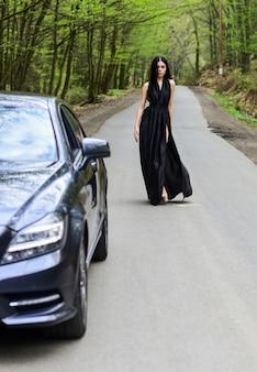 Reise starten. luxusauto. auto und ziemlich sexy frau an der straße. reisekonzept. reisen und urlaub. transportkonzept. mit dem auto reisen. autoservice. status und respekt. lebensstil der reichen leute.